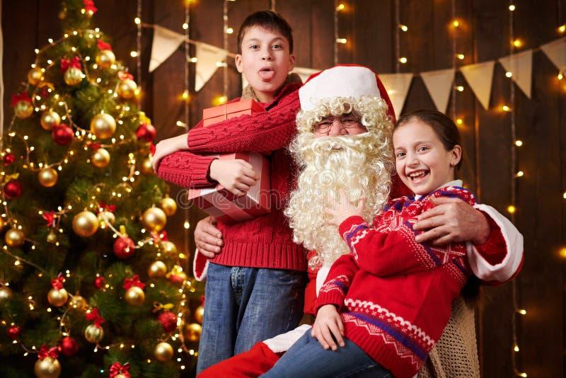Санта-Клаус и мальчик и девочка, позирующие вместе в помещении, рядом с декорированным xmas деревом с огнями, разговаривают, улыб стоковое фото
