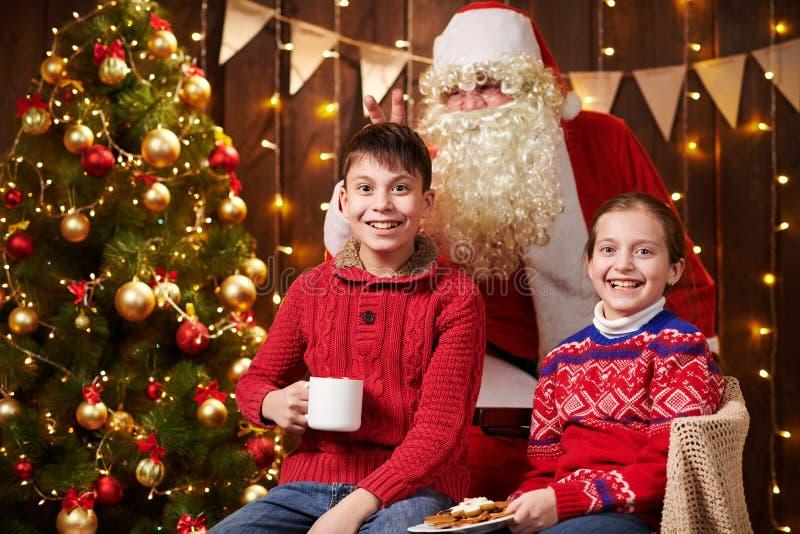 Санта-Клаус и мальчик и девочка, позирующие вместе в помещении, рядом с декорированным xmas деревом с огнями, разговаривают, улыб стоковые фотографии rf