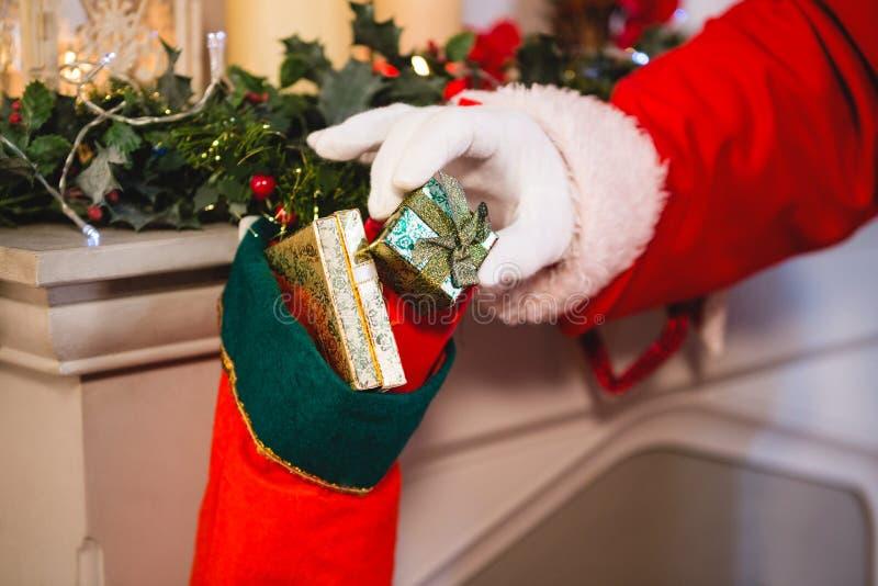 Санта Клаус кладя подарок в чулок рождества стоковые изображения