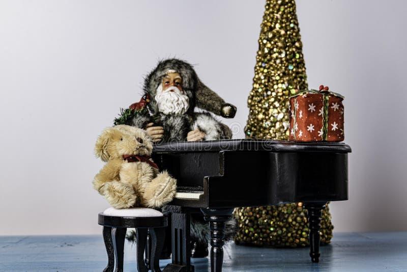 Санта Клаус полагаясь против рояля с заполненным медведем стоковое изображение