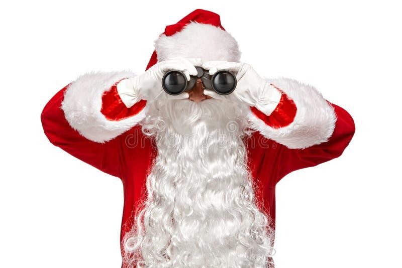 Санта Клаус смотря через бинокли Изолят на белой предпосылке стоковое изображение