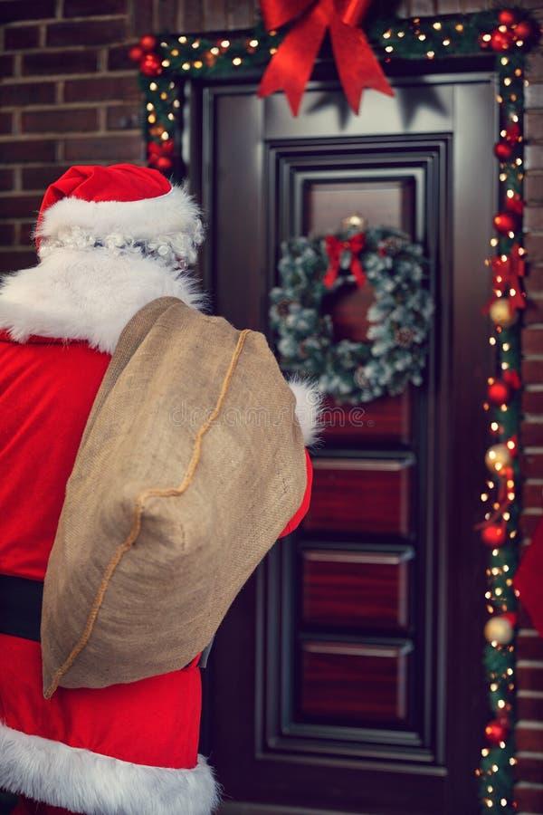 Санта Клаус с большим мешком перед домом, задним взглядом стоковые изображения