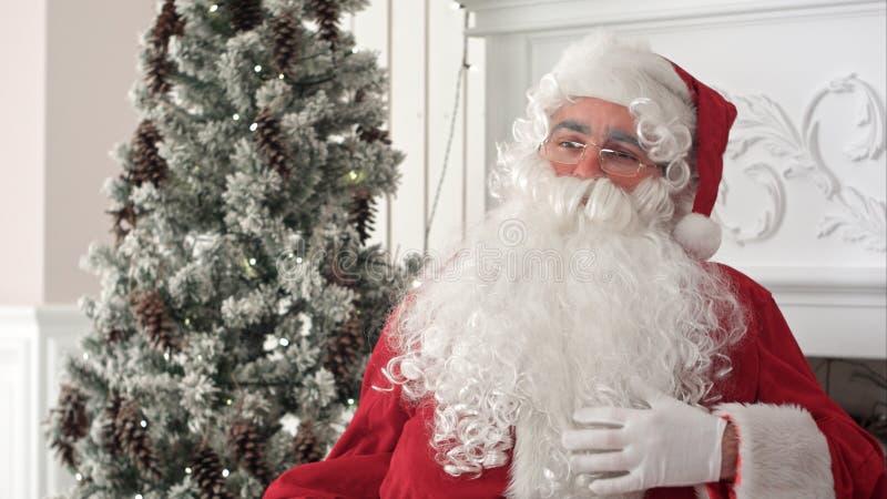 Санта Клаус штрихуя его борода снега белая думая около chidlren желания стоковое фото