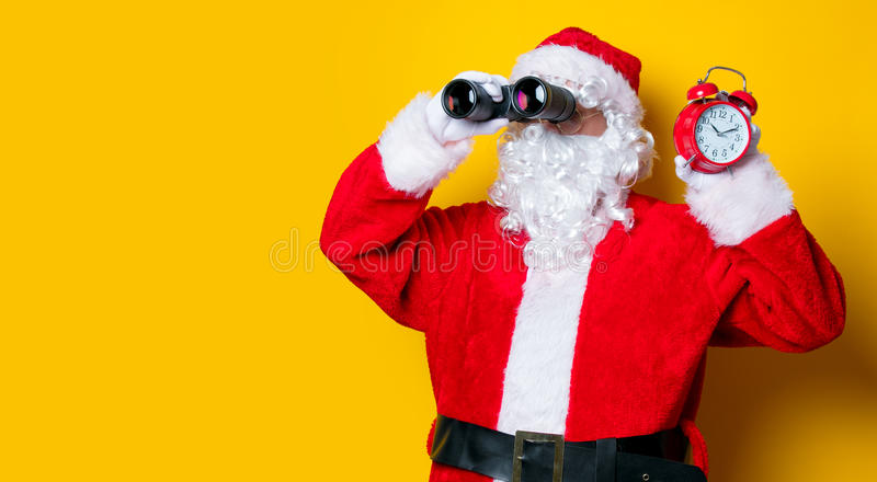 Санта Клаус держа бинокли и будильник стоковое изображение