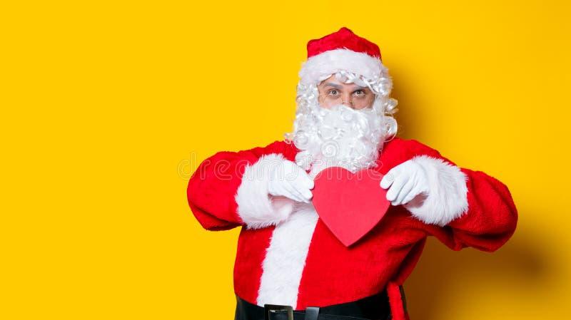 Санта Клаус держа подарок формы сердца стоковое фото rf