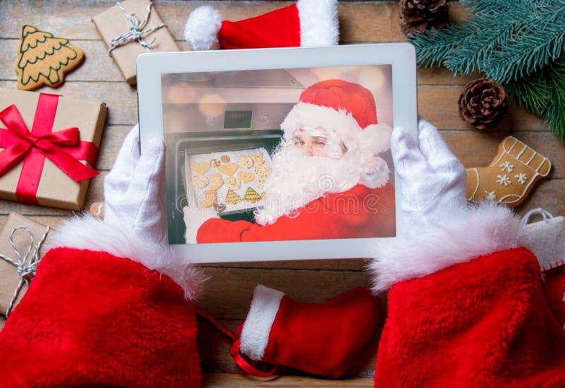 Санта Клаус держа прибор таблетки стоковая фотография