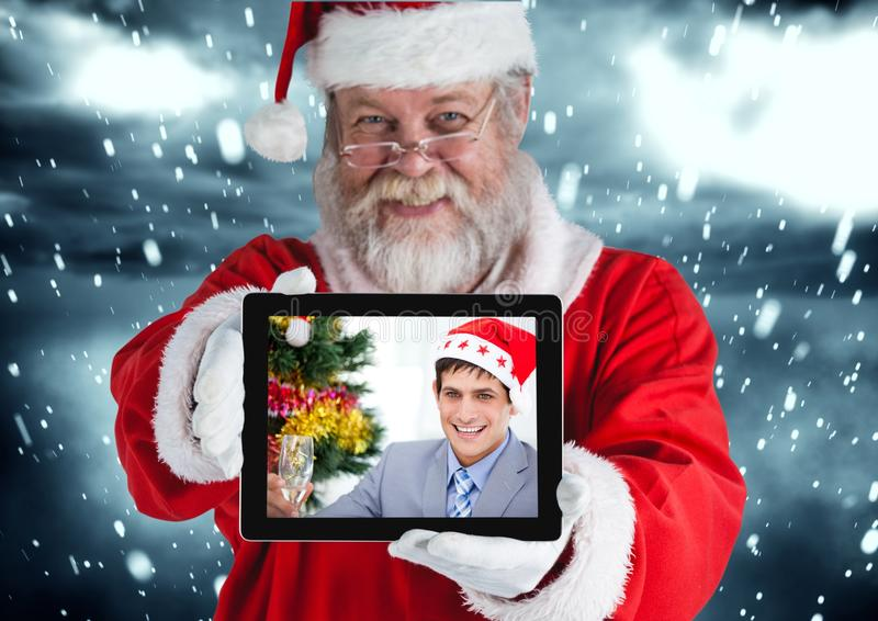 Санта Клаус держа цифровую таблетку с фото человека стоковые фото