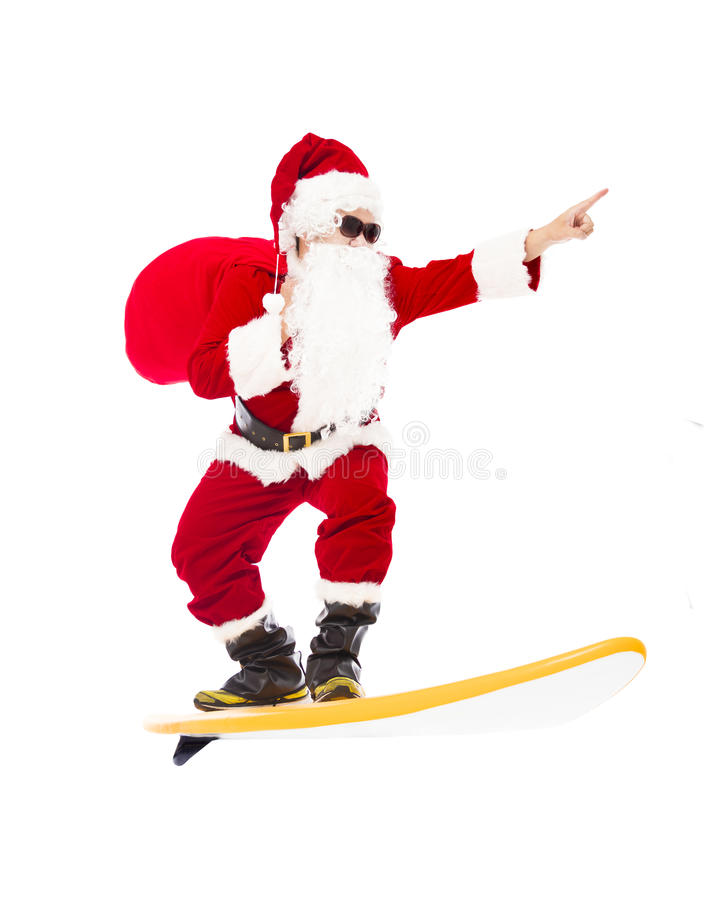 Санта Клаус занимаясь серфингом с доской прибоя стоковое изображение rf