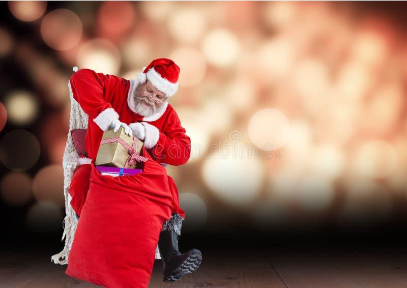 Санта Клаус извлекая подарок от мешка пока сидящ в стуле стоковые фото