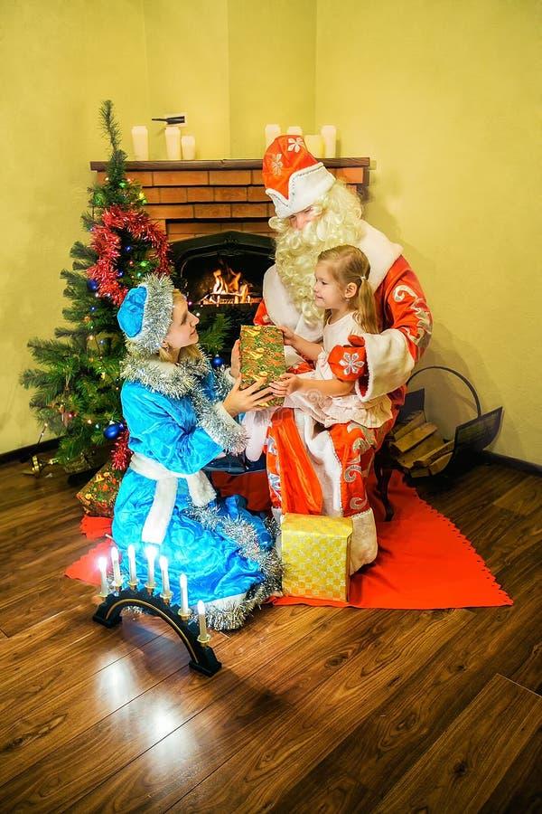 Санта Клаус и девушка снега представили подарок к девушке Время 5 стоковые фотографии rf