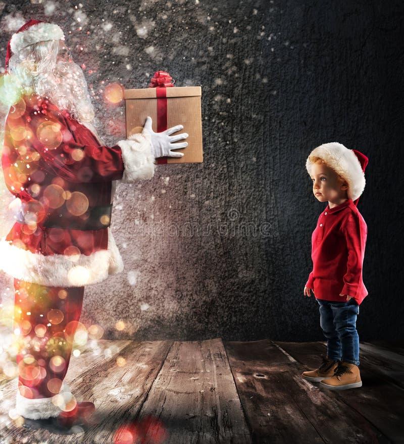 Санта Клаус поставляет подарок к ребенку стоковое фото rf