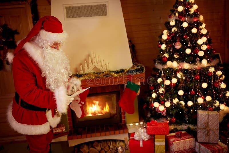 Санта Клаус противостоит рождество и большой стог подарочных коробок стоковое изображение rf