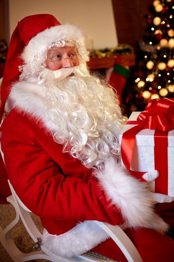Санта Клаус сидя и держа большая коробка с подарком стоковое изображение