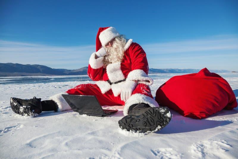 Download Санта Клаус сидя на снеге, смотря новости компьтер-книжки Стоковое Фото - изображение насчитывающей человек, книжка: 40591336