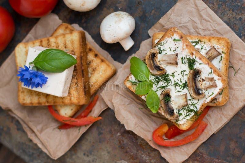 Сандвичи состоя из здравицы с зажаренными зажаренными грибами и расплавленными специями сыра старая таблица Взгляд сверху Конец-в стоковые изображения rf
