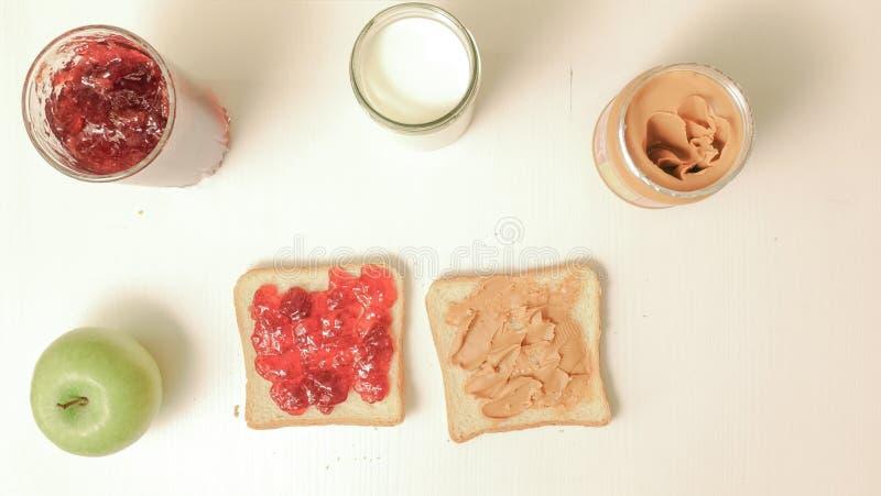 Сандвичи с вареньем, арахисовым маслом, стеклом молока и яблоком стоковое фото rf