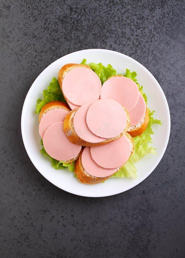 Сандвичи с докторской сосиской в белой плите стоковые фотографии rf