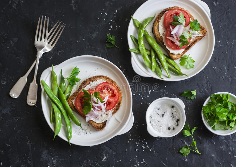 Сандвичи томата и сыра и зеленые фасоли здоровые вегетарианские завтрак или закуска на темной таблице, взгляд сверху стоковая фотография