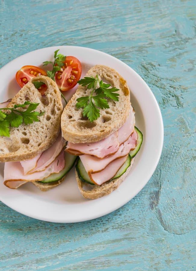 Сандвич с всеми хлебом, огурцом и ветчиной зерна на белой плите стоковая фотография rf
