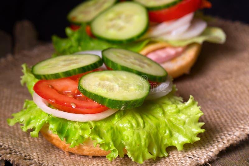 Сандвич с салатом и другими овощами на деревянном столе и a стоковая фотография