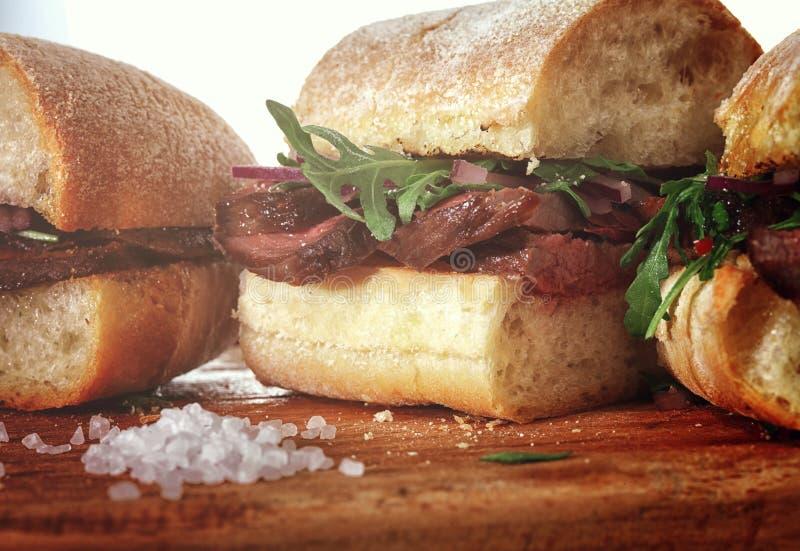 Сандвич с стейком говядины на деревянной стойке стоковые изображения