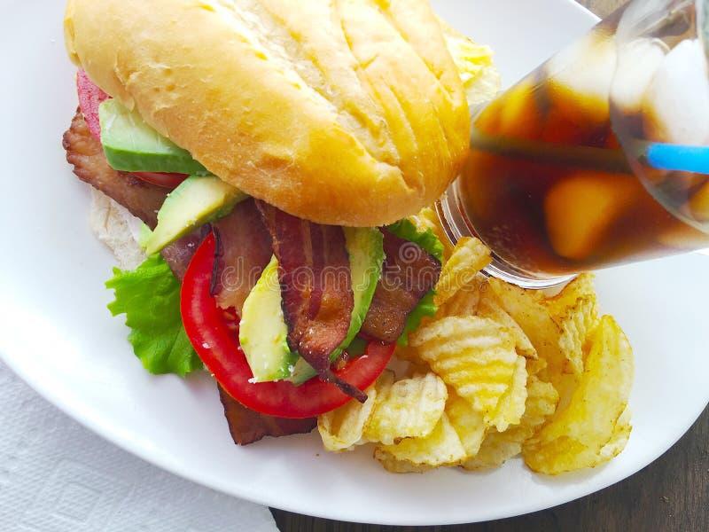 Сандвич BLT с авокадоом, обломоками и колой стоковая фотография rf