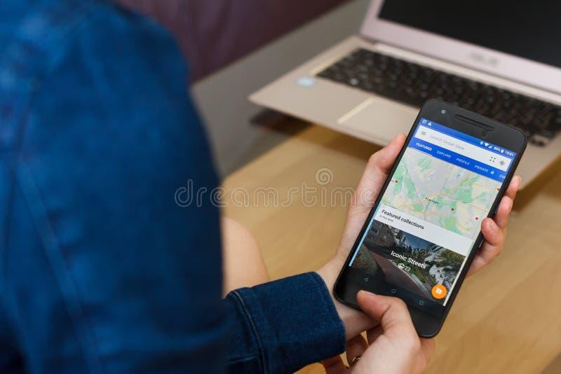 САН-ФРАНЦИСКО, США - 22-ое апреля 2019: Конец до женских рук держа смартфон используя применение взгляда улицы Google, Сан-Франци стоковые изображения