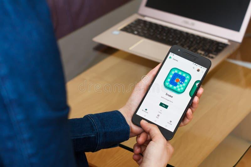 САН-ФРАНЦИСКО, США - 22-ое апреля 2019: Конец до женских рук держа смартфон используя применение игр игры Google, Сан-Франциско стоковое изображение