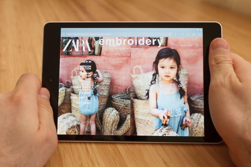 САН-ФРАНЦИСКО, США - 1-ое апреля 2019: Конец до рук держа планшет используя интернет и смотря через вебсайт Zara, в Сан стоковое изображение