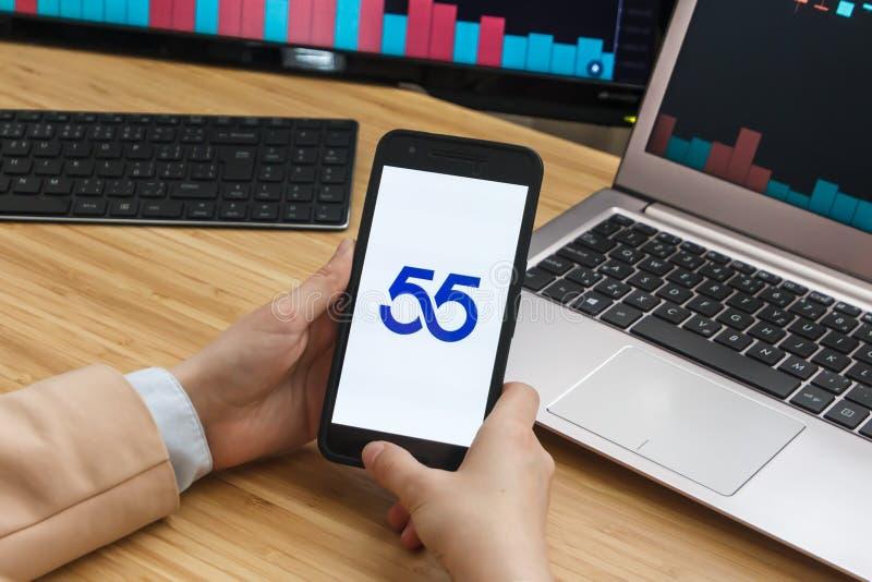 САН-ФРАНЦИСКО, США - 18-ое июня 2019: Женские руки торговца держа смартфон используя применение 55 мировых рынков Cryptocurrency стоковые фото