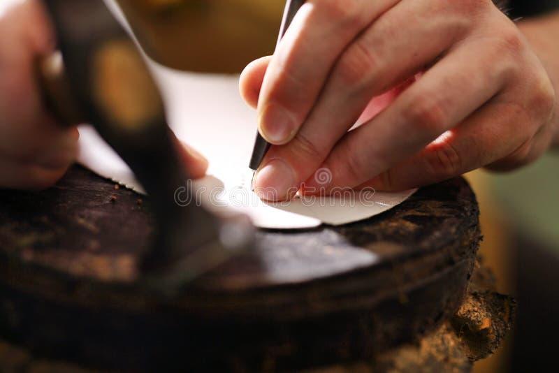 Сапожник делает отверстия зубила в зерне кожи стоковые изображения