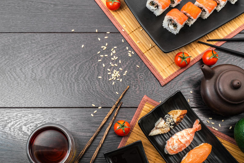 Сасими суш установленные и крены и томаты суш служили на темной предпосылке стоковые фото