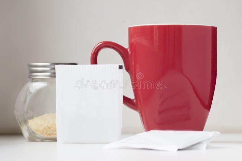 Саше чая с чашка и желтым сахарным песком пакетика чая красными стоковые изображения rf