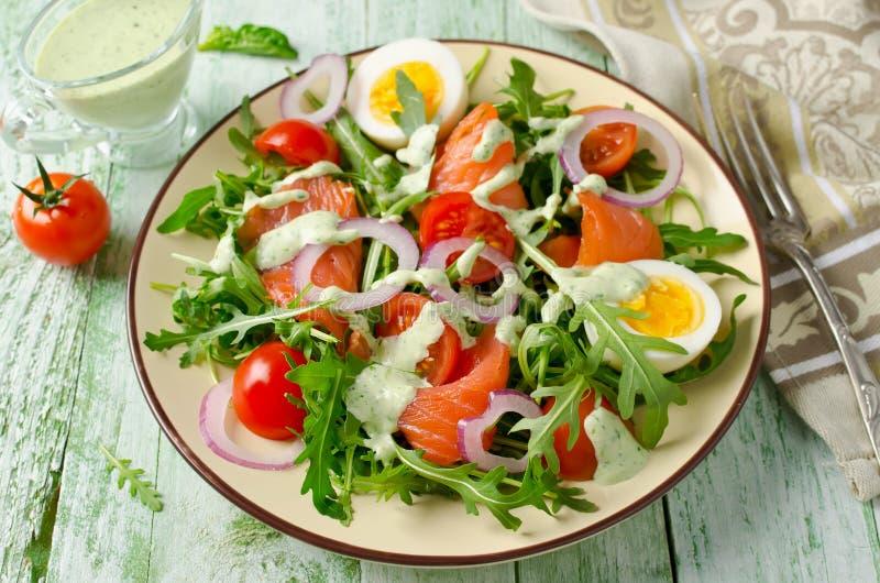 Салат копченых семг с arugula, томатами, яичками и красным луком стоковое изображение