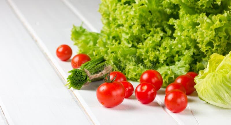 Салат салата, томаты и зеленый лук на белой предпосылке стоковые изображения