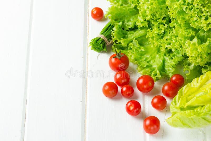 Салат салата, томаты и зеленый лук на белой предпосылке стоковая фотография