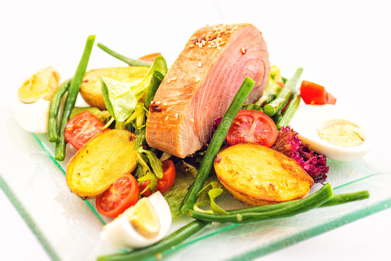 Салат свежего овоща с томатами, картошками, яичками, зелеными фасолями и зажаренным стейком тунца на стеклянной пластинке изолиро стоковое фото