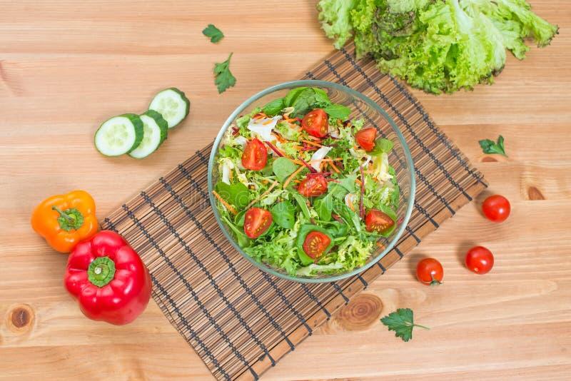 Салат свежих овощей и зеленого цвета на деревянной предпосылке, взгляд сверху стоковая фотография