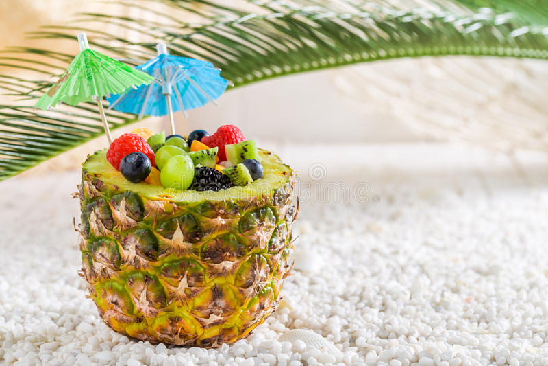 Салат свежих фруктов в ананасе с зонтиками коктеиля на пляже стоковое изображение rf