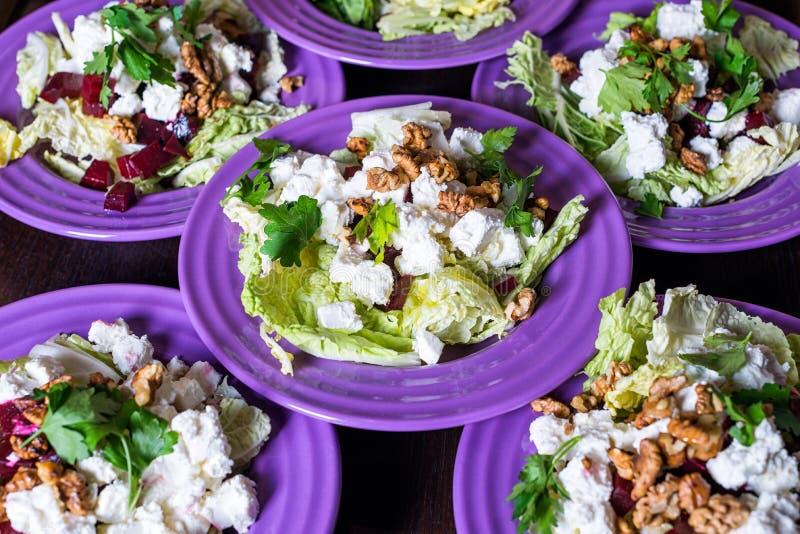 Салат свеклы с козий сыром, грецкими орехами, зелеными цветами и травами и оливковым маслом стоковое фото rf
