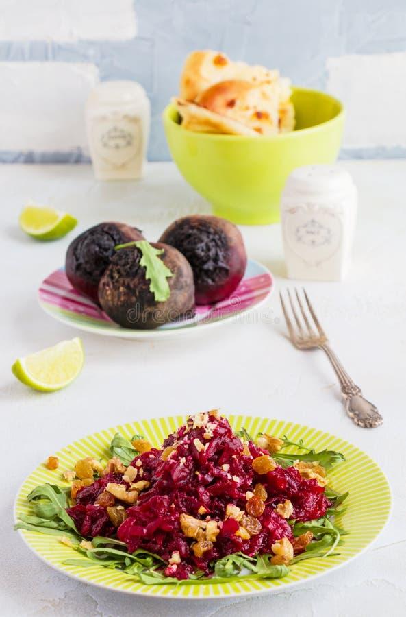 Салат с испеченными свеклами, arugula, изюминками и грецкими орехами на зеленой плите на таблице в кухне Все бураки, известка, св стоковая фотография rf