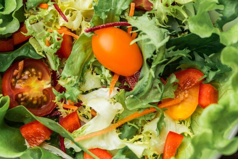 Салат с свежими овощами - томатами, морковами, болгарскими перцами и смешанными зелеными цветами - arugula, mesclun, mache стоковое изображение rf