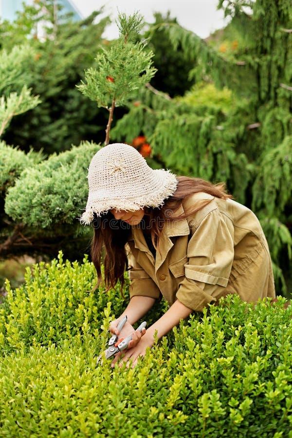 Садовник девушки в одеждах и соломенной шляпе деятельности стоковые изображения