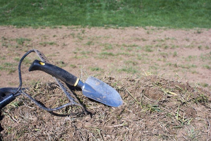 Садовничая инструменты на куче грязи и трав стоковые изображения rf