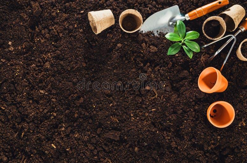 Садовничая инструменты на почве сада текстурируют взгляд сверху предпосылки стоковые фотографии rf
