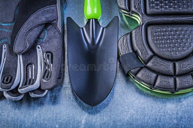 Садовничая лопаткоулавливатель руки протекторов колена перчаток безопасности на металлическом стоковое фото rf