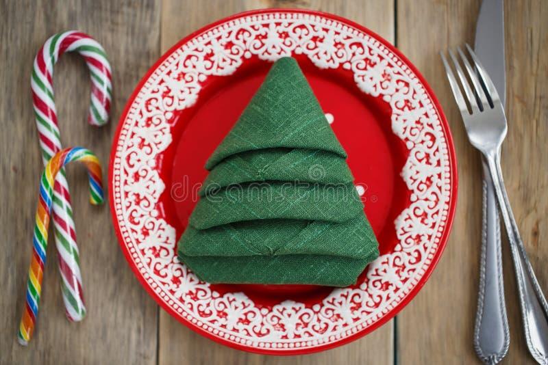 Салфетка сложила в форме рождественской елки в красной плите стоковое фото rf