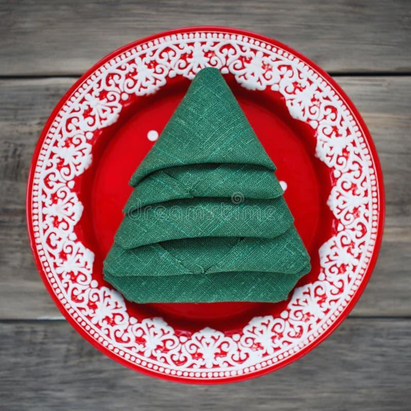Салфетка сложила в форме рождественской елки в красной плите стоковые фотографии rf