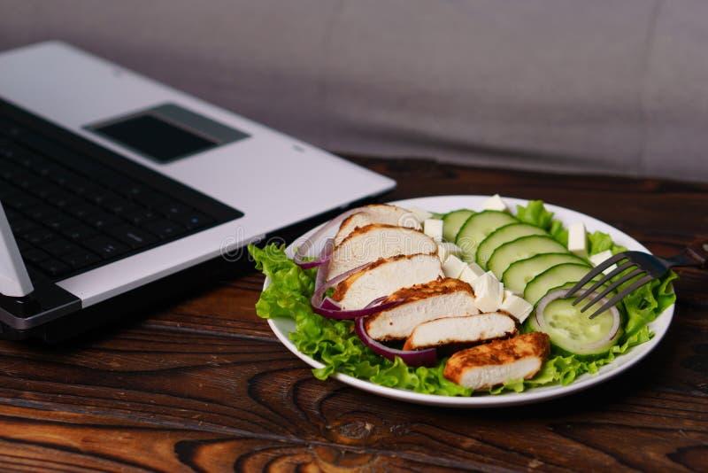 Сбалансированная еда салат и цыпленок около ноутбука стоковая фотография rf