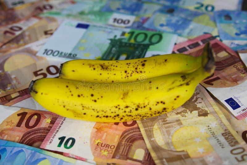 Сбалансированная здоровая концепция цены питания - 2 желтое и коричневые зрелые бананы на бумажных деньгах денег бумаги евро стоковые фотографии rf